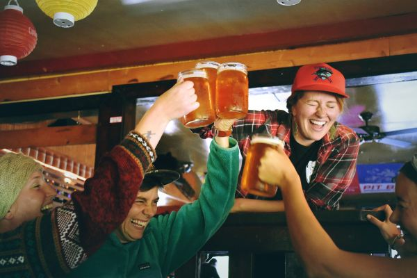 A group of laughing people cheers mason jars full of beer