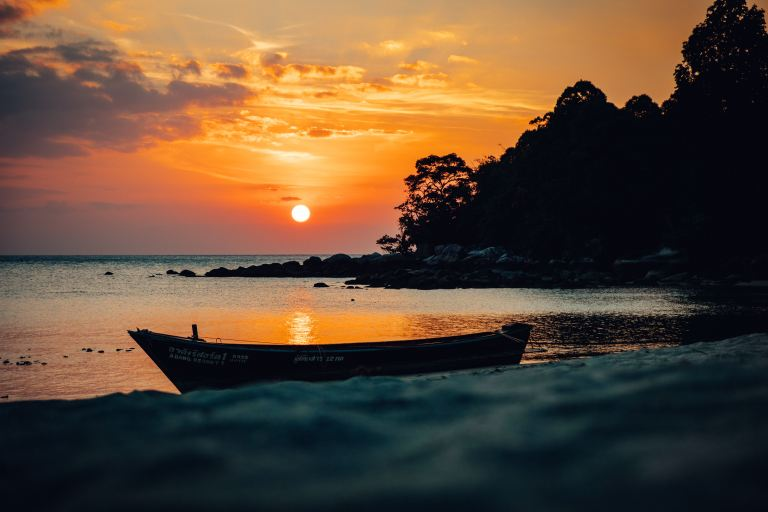 A boat onshore at sunset on Thai island of Koh Lipe