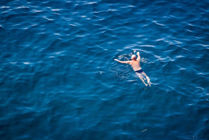 "An old man swimming in the ocean in affectionately named ""budgey smugglers"" in accordance with one of France's wierd laws"