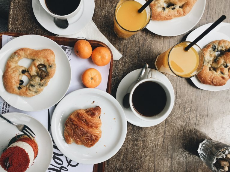A mix of sweet and savoury pastries with juice and coffee in Hungary