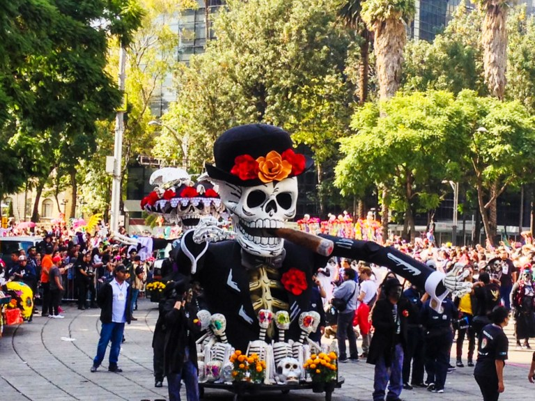 A large skeleton shaped float in Mexico cities Day of the Dead parade.
