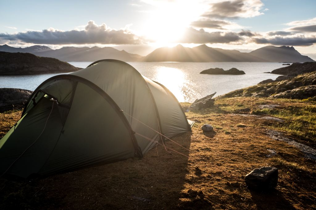 A tent next to a large lake where people are camping in Norway