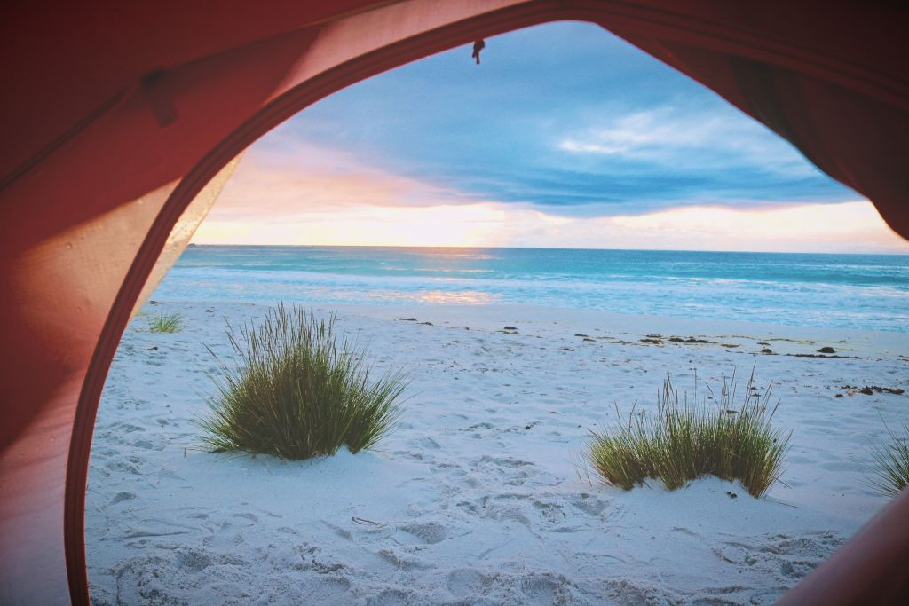 View of a white sand beach and the ocean from inside a tent in Australia