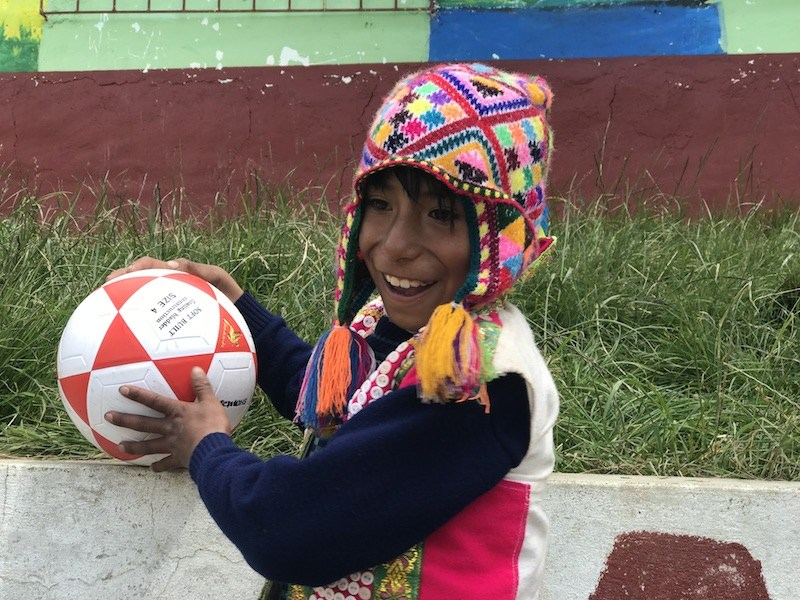 A young Peruvian boy playing with a football ball