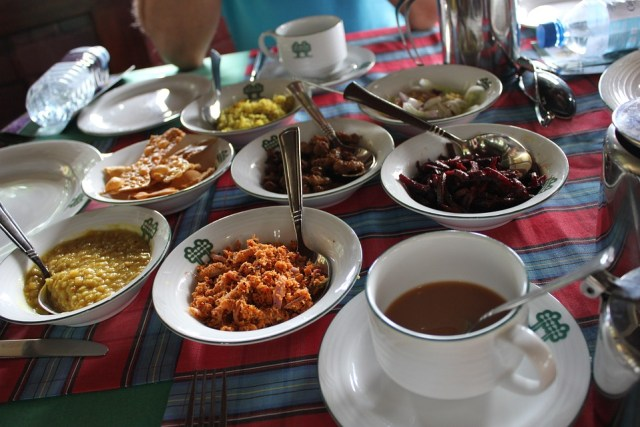 A table with curries, dried chillies, coffee and other dishes