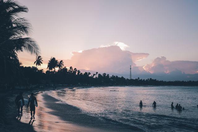 Surfers walking along Arugam bay at sunset