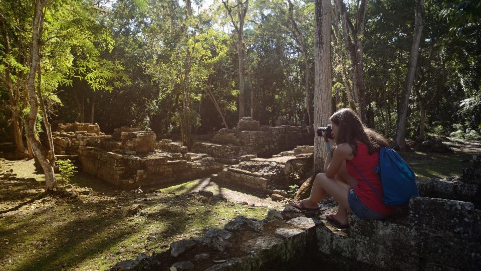Woman photographing ancient Mayan ruins in Copan in Honduras