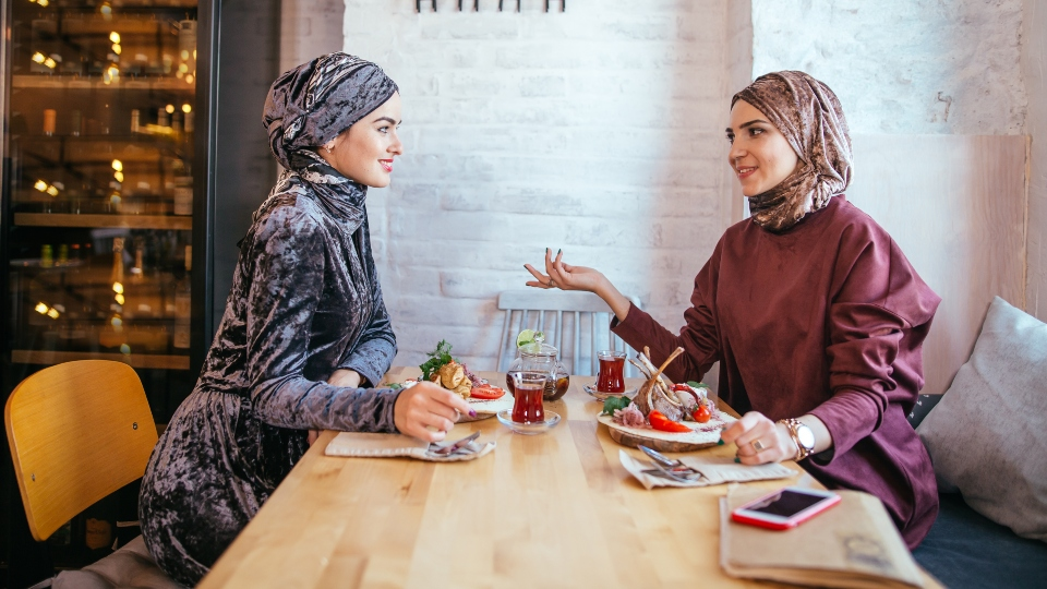 Two Muslim women in cafe, friends meeting