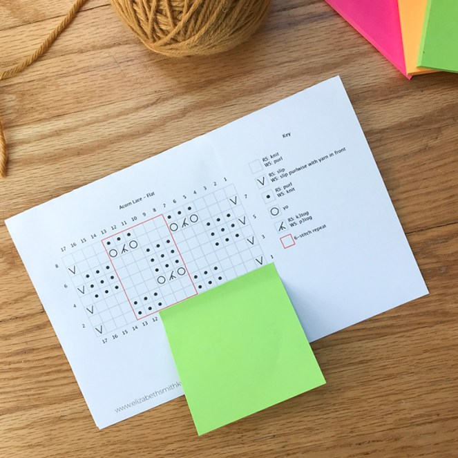 photo showing a brightly colored post it note covering lines of a lace knitting pattern to help a knitter keep track of their rows