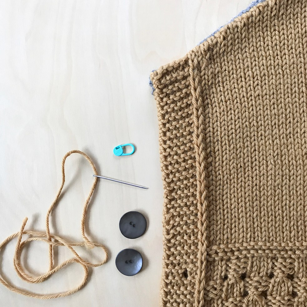 flat lay of a poncho front with buttons and yarn threaded on a needle