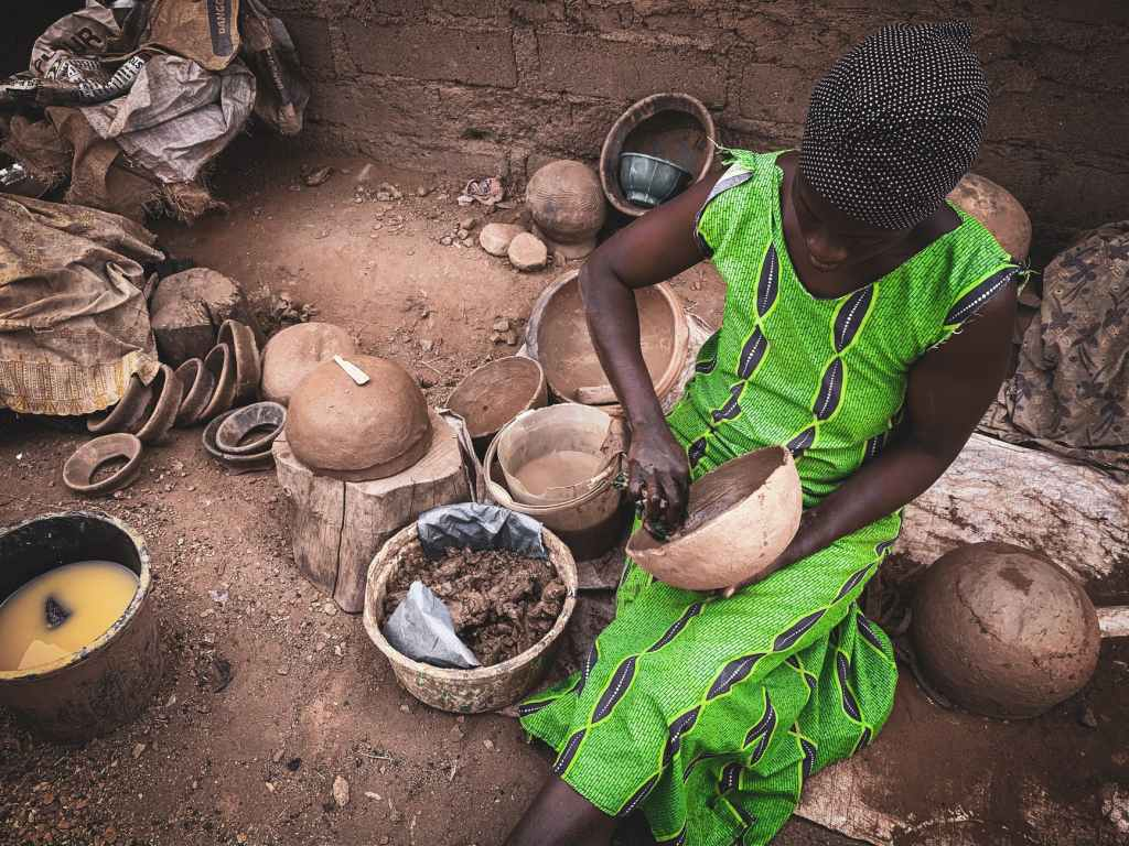 ethnic craftswoman creating pottery in rustic workshop