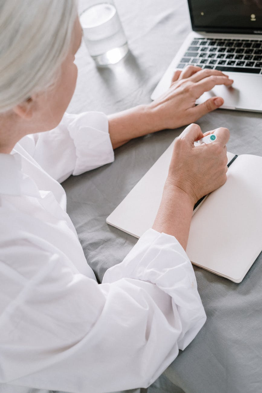 an elderly woman taking notes while using a laptop
