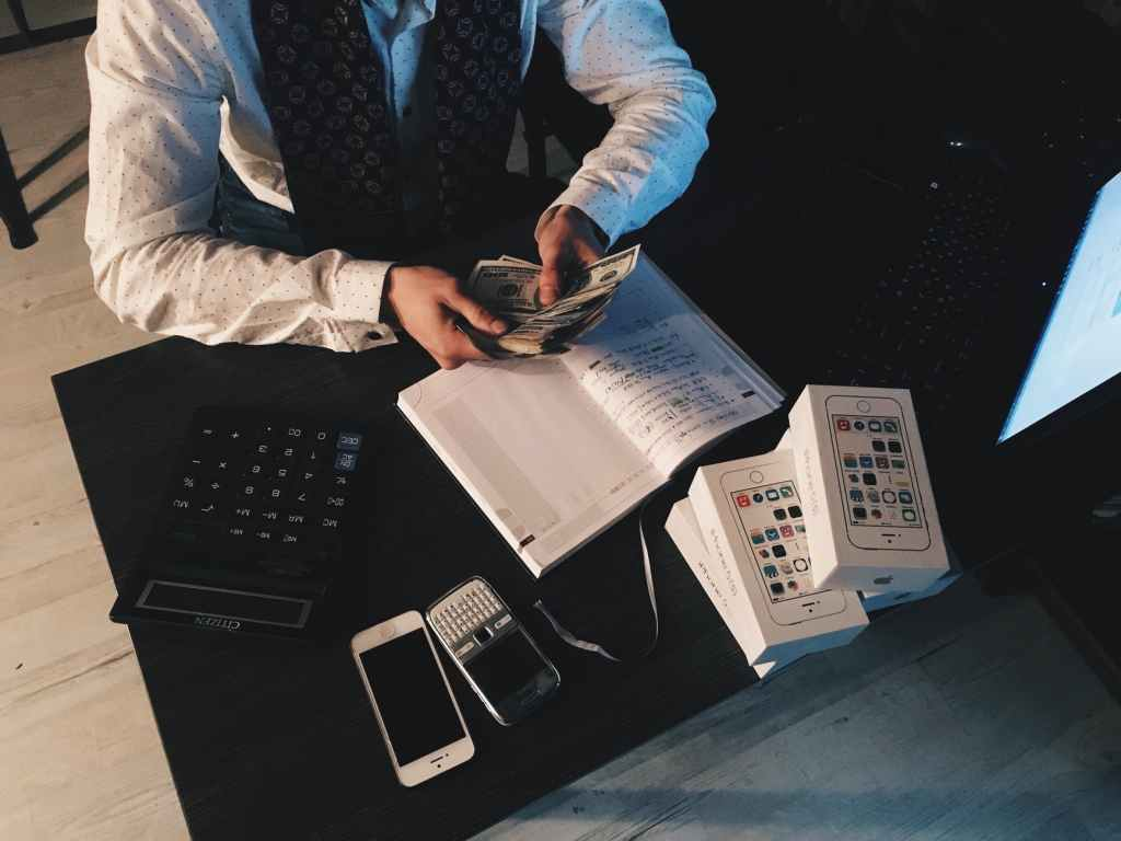 person counting money with smartphones in front on desk