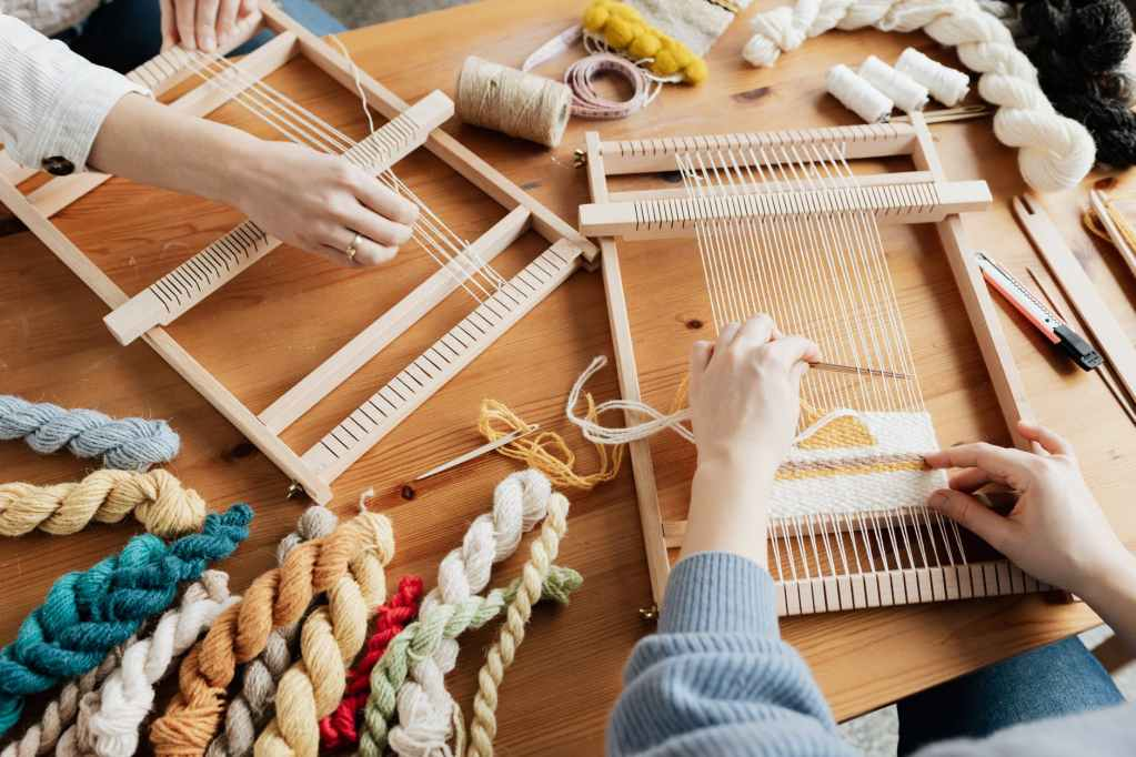 photo of two person s hands weaving