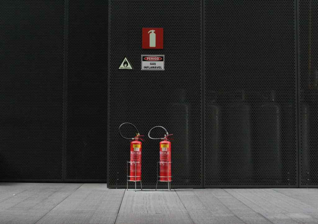 pair of red fire extinguisher tanks in front of black wall