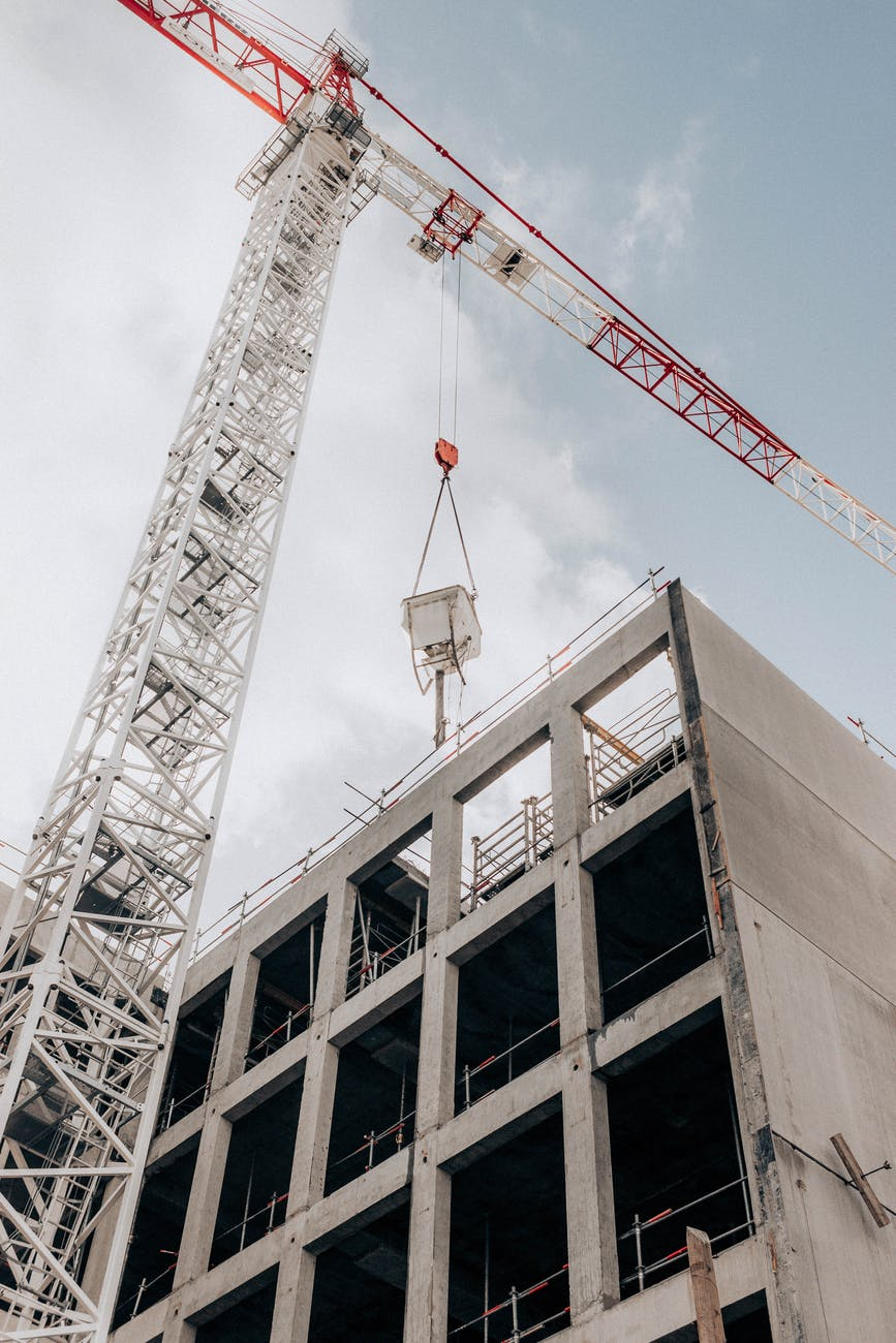 half built multistage building and crane tower at construction area against cloudy sky