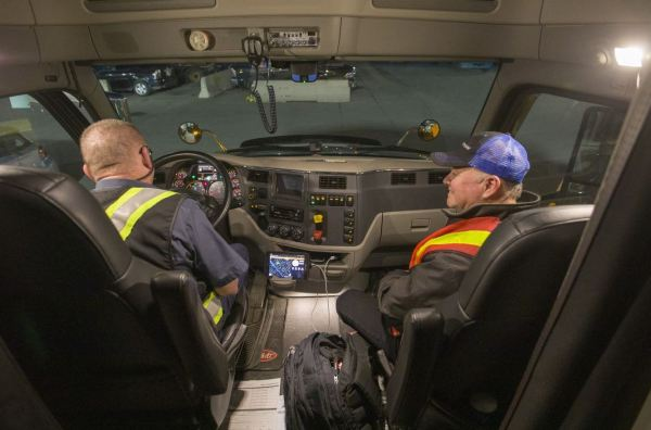 Truck driver filling out a report in a mobile device with Marc Moncion in the  passenger seat.