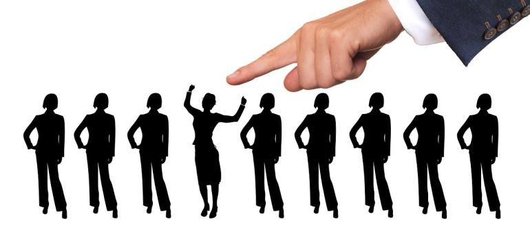 O que é clima organizacional: vetores de pessoas na mesma posição, enquanto uma mão de um gestor aponta para o destaque do grupo: a pessoa em destaque está em uma posição diferente das demais.
