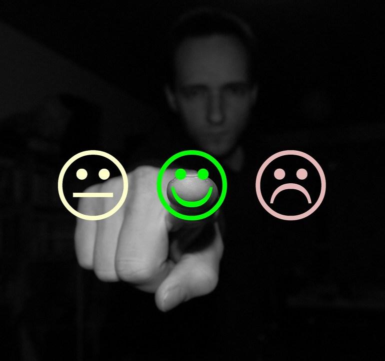 três círculos com carinhas de regular, bom e ruim com homem apontando para a carinha do bom em uma pesquisa de satisfação