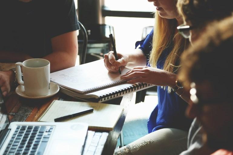 pessoas sentadas ao redor de uma mesa com cadernos e escrevendo