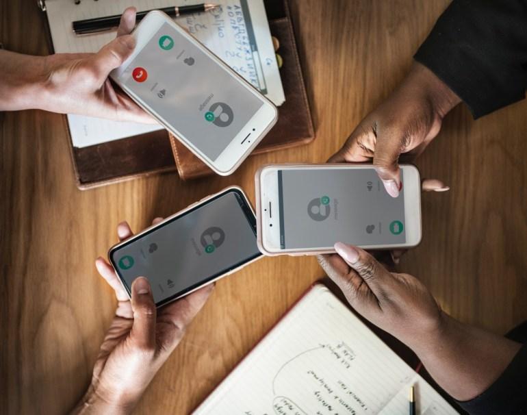 Três mãos de pessoas segurando um celular utilizando o mesmo app