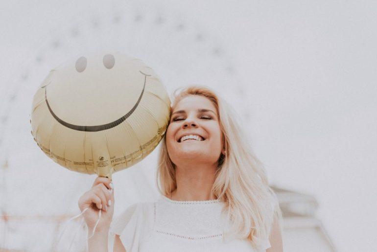 Mulher sorrindo com um balão de smiles feliz