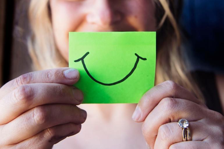 Mulher com um smile desenhado em um papel
