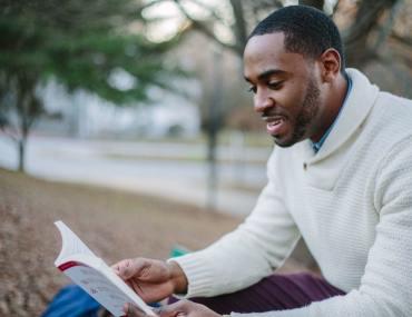Homem lendo livro de customer sucess