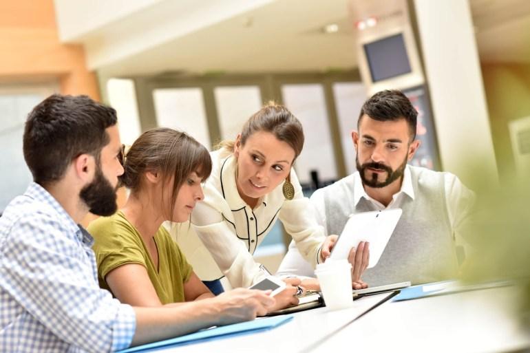 Dois homens e duas mulheres reunidos em volta de uma mesa, fazendo planos