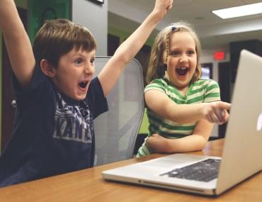 Crianças vibrando ao olhar tela do computador
