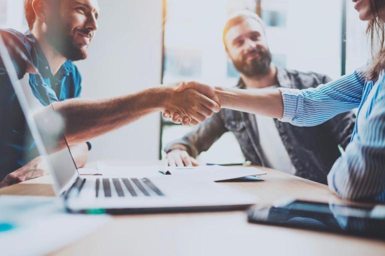 Colaboradores apertando as mãos no ambiente de trabalho