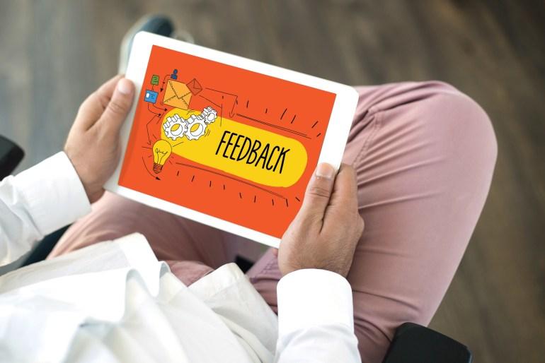 homem segurando tablet com feedback aberto na tela