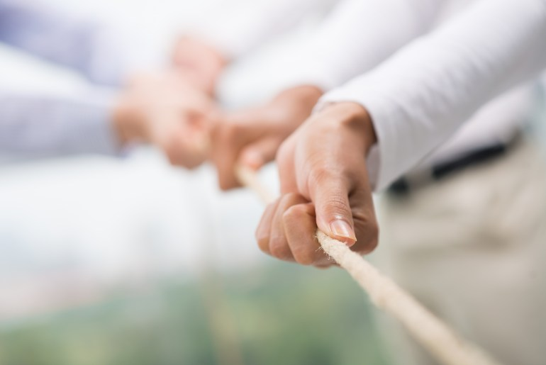 Equipe puxando corda juntos