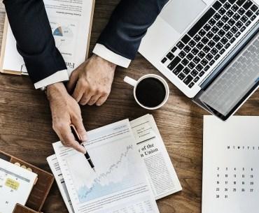 Homem vendo dados e planilhas de pesquisa de satisfação em escritório de contabilidade