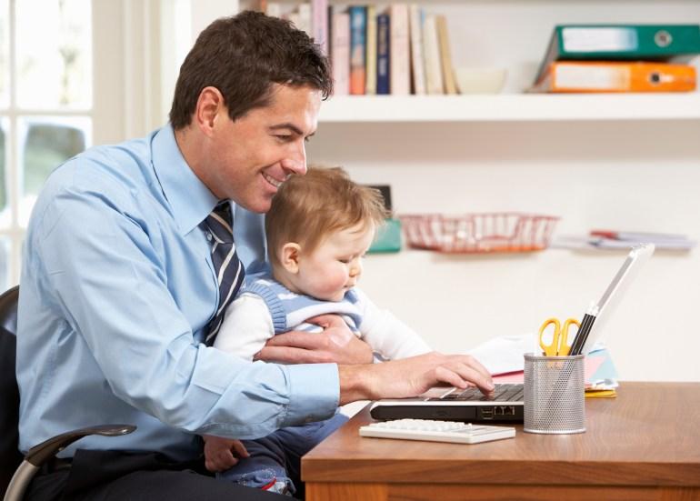Funcionário feliz trabalhando de home office com o filho no colo