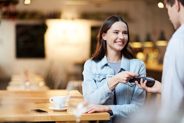 Cliente feliz fazendo pagamento em restaurante.