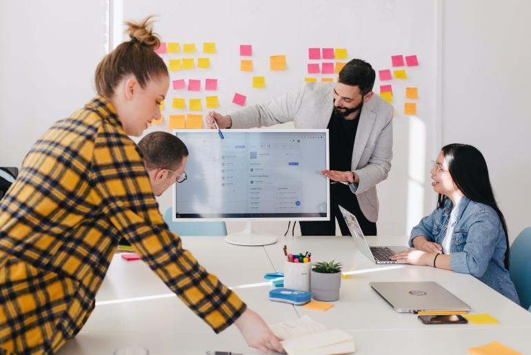 Equipe de trabalho analisando métodos de pesquisa para definir a jornada do consumidor.