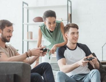 Grupo de amigos sorridentes jogando video-game.