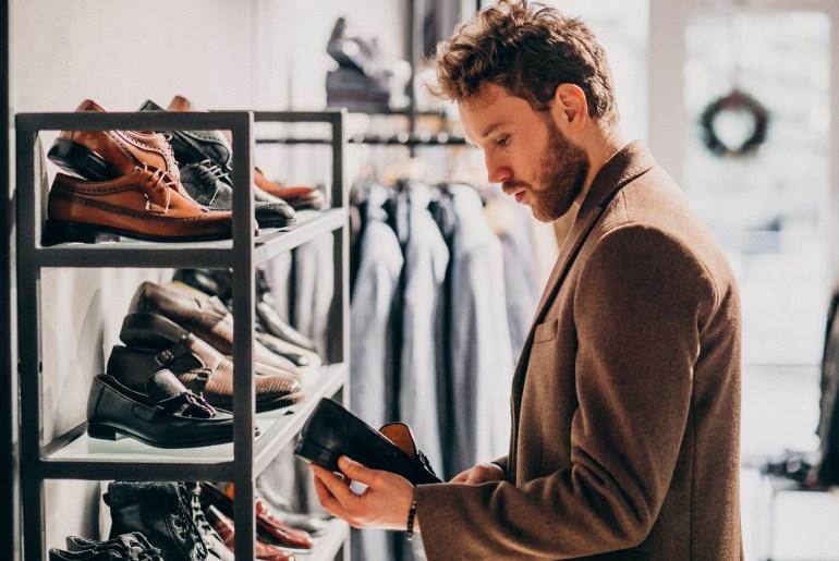 Homem analisando sapatos em loja