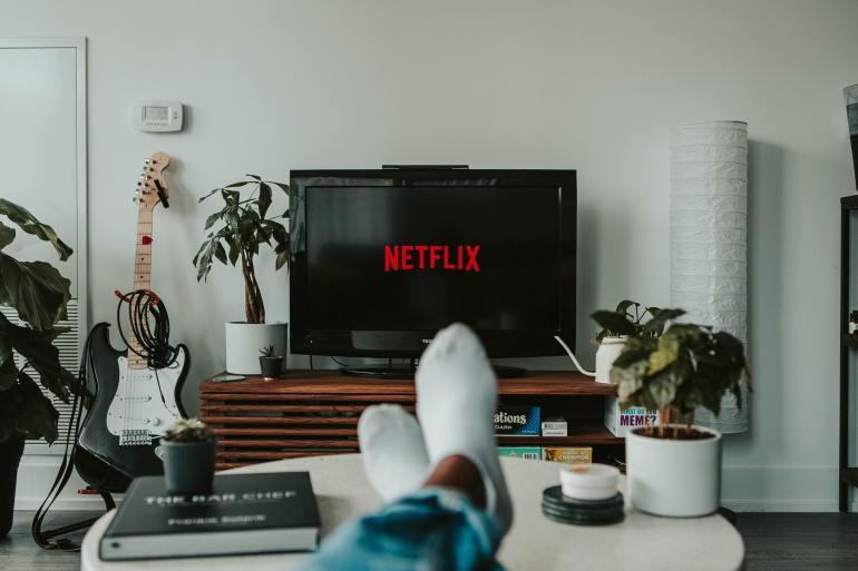 Homem de meias assistindo Netflix.