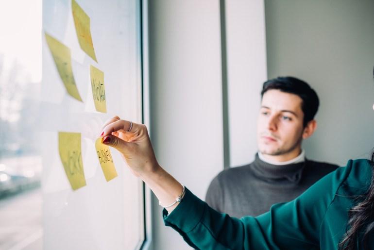 Colegas de trabalho analisam estratégias de jornada do cliente.