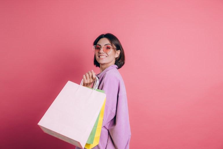 cliente satisfeita, segurando sacola de compras e sorrindo em frente a fundo rosa