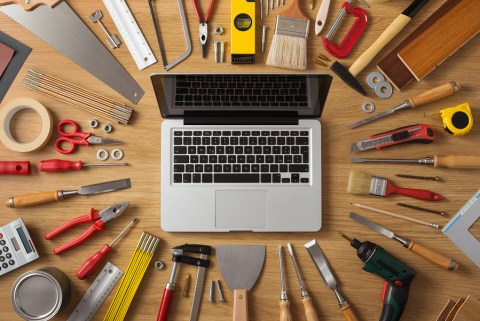 Laptop on a work table with DIY and construction tools all around top view hobby and crafts concept