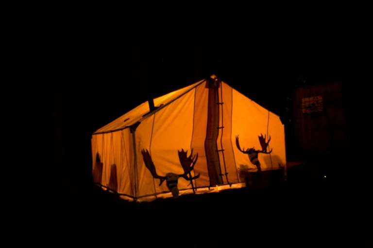A tent lighted from the inside showing hunting trophies