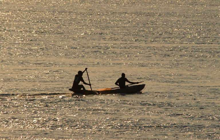 African fishermen in traditional dugout canoe