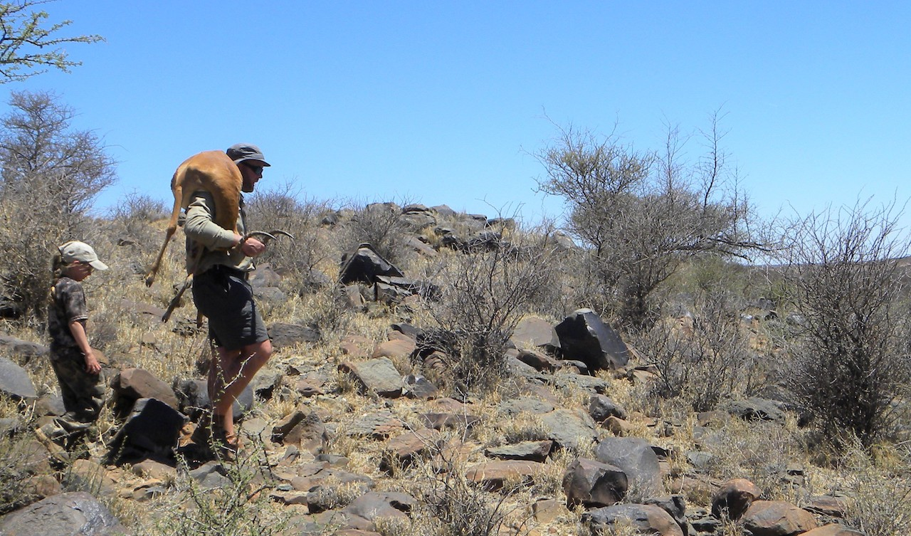 PH carrying a harvested antelope on his shoulders