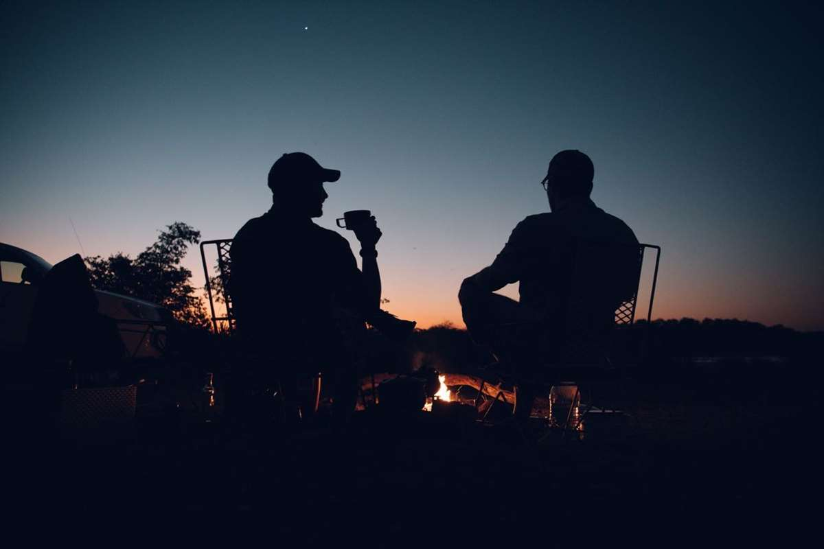 Two hunters at a campfire in Africa