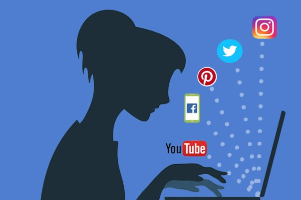 silhouette of a woman typing at a laptop with social media platforms jumping off of the screen.