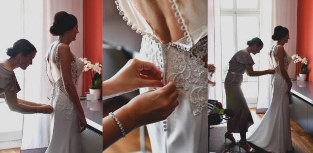 Die Braut schluepft in ihr Brautkleid und der Hochzeitsfotograf macht die Bilder.