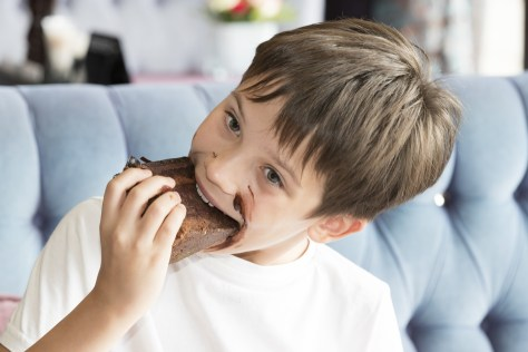 Smiling boy eating a piece of choclate cake